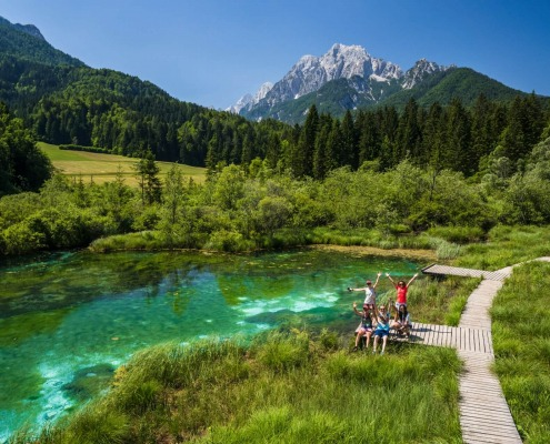 Happy Group of Friends are raising Hands Up at Zelenci Lake, Slovenia