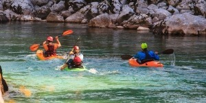 Emerald kayaking Slovenia three kayakers on Soča river.