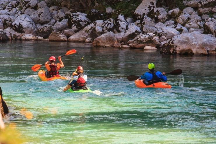 Emerald kayaking Slovenia three kayakers on Soča river.