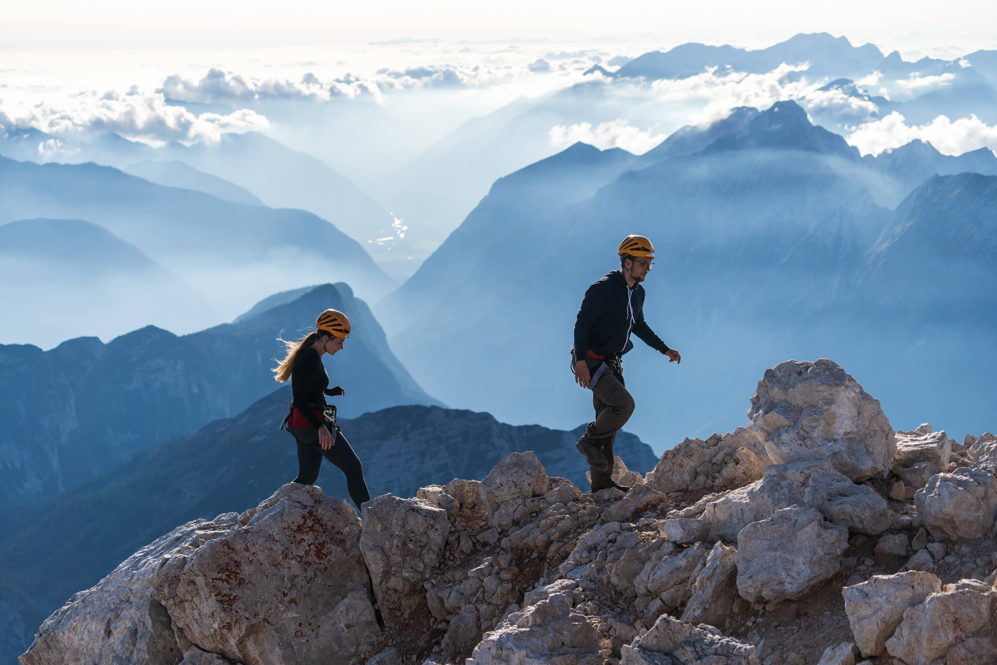 Couple Hikers Ascending Triglav Mountain from Planika hut, Soca Valley on the Background