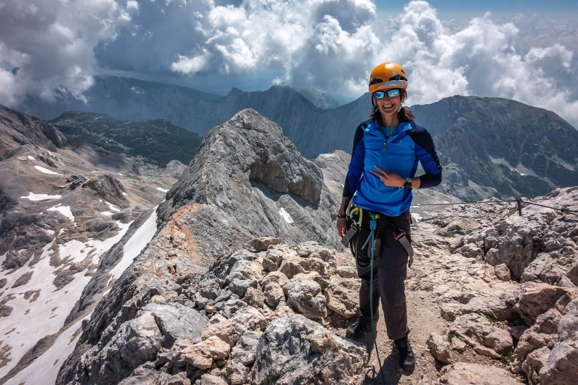 Happy Female Climber Ascending Triglav Peak, Small Triglav on the Background