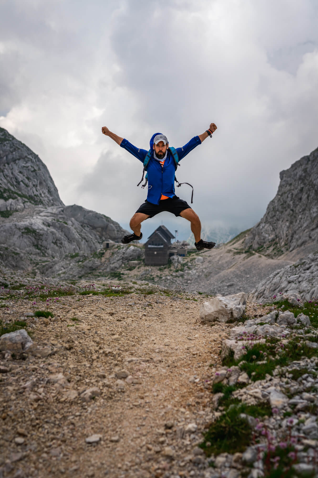 Hiker with Blue Jacket is Jumping above Dolic Hut, Julian Alps